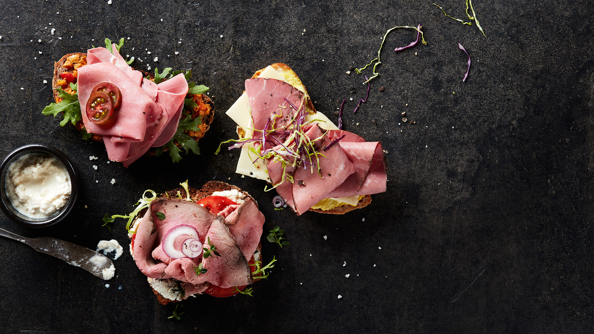 Three gourmet deli meat sandwiches made from Columbus Corned Beef, Roast Beef, and Pastrami with horseradish sauce on the side
