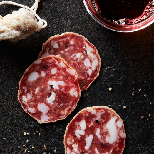 Three slices of Columbus Salami on a black slate sprinkled with black peppercorns and a glass of red wine