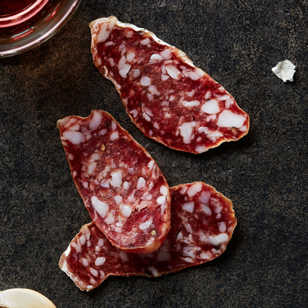 Delicious Columbus Cacciatore Salami on black slate with garlic cloves and a glass of medium-bodied red wine