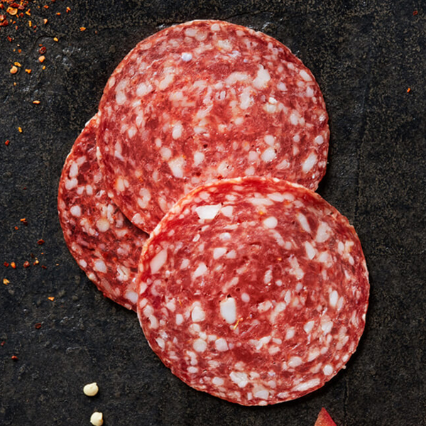 Savory Columbus Calabrese Salami on black slate with sliced red bell pepper and a scattering of crushed red pepper flakes
