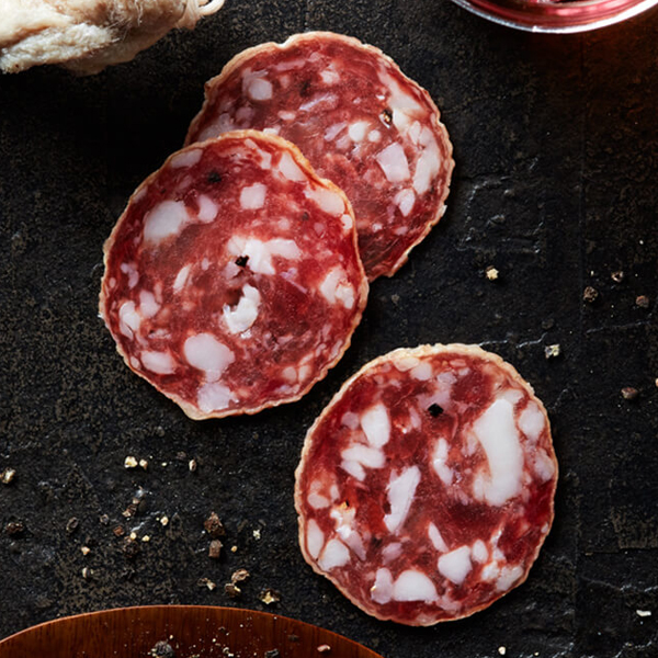 Sliced Columbus Felino Salami on black slate with a plate of crushed black peppercorns, dry aged Felino, and a glass of medium-bodied red wine