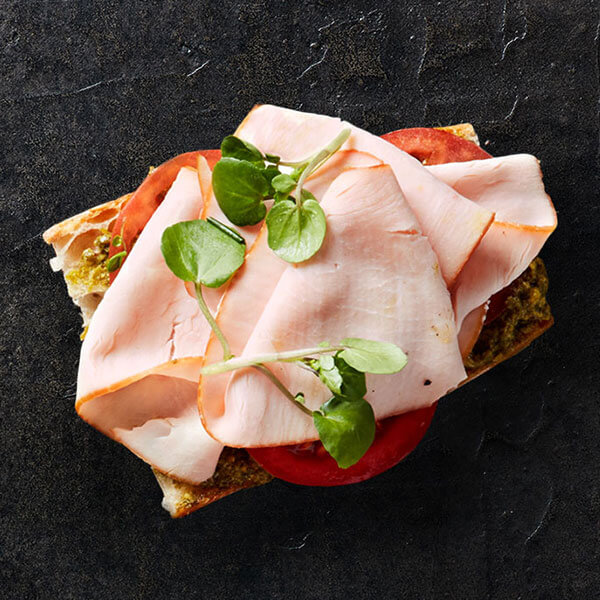 An open-faced Columbus Hickory Smoked Turkey sandwich resting on a bed of sliced tomatoes, whole grain mustard, and topped with herbs