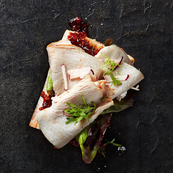 An open-faced Columbus Holiday Carving Turkey sandwich resting on a bed of greens, pomegranate jelly, and topped with herbs