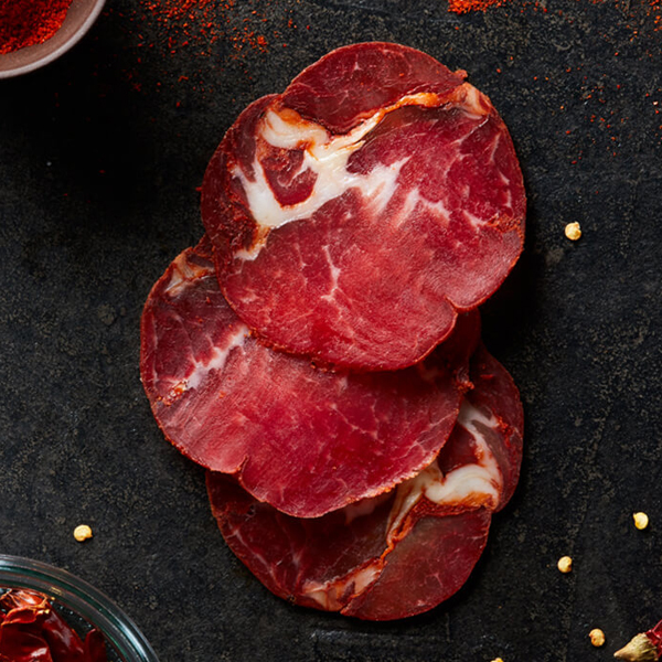 Sliced Columbus Hot Coppa on black slate with a bowl of paprika and a bowl of dried red chiles with the seeds spilling out
