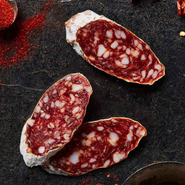 Thick sliced Columbus Hot Sopressata on black slate with a spoonful of paprika, dried chiles, and crushed red pepper flakes