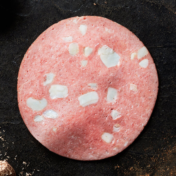 A slice of Columbus Mortadella on black slate with three sticks of cinnamon next to a bowl of ground cinnamon and three pieces of walnut