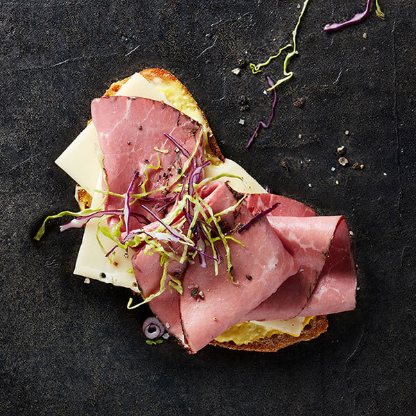 An open-faced Columbus Pastrami sandwich on a black slate topped with cabbage, red onions, mustard, and Swiss cheese