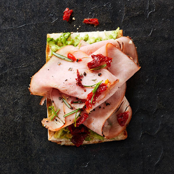An open-faced Columbus Peppered Turkey sandwich topped with sun-dried tomatoes, rosemary, and avocado