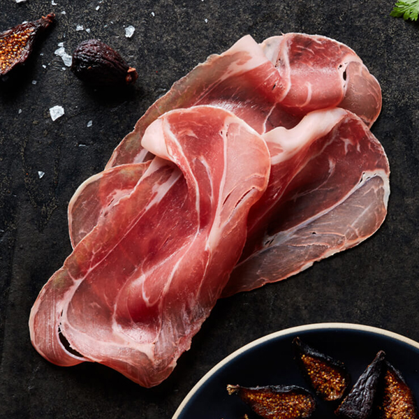 Sliced and folded Columbus Prosciutto on black slate next to a plate of opened figs