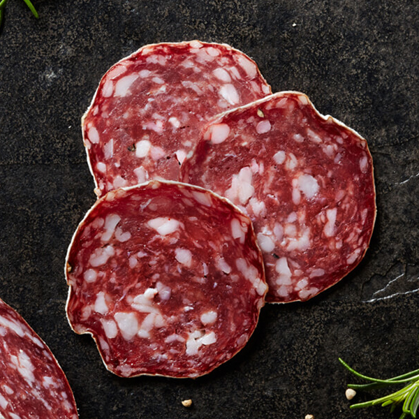 Sliced Columbus Rosette De Lyon Salami on black slate with crushed white peppercorns and a sprig of rosemary