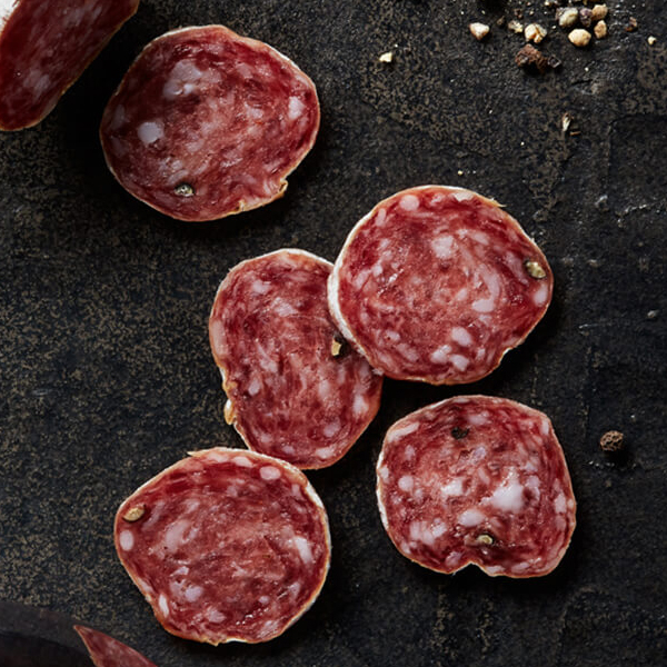 Fresh sliced Columbus Secchi Salami on black slate with crushed peppercorns and a glass of medium-bodied red wine