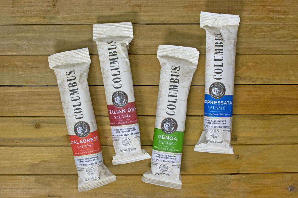 Four Columbus Salami samplers on a wooden background